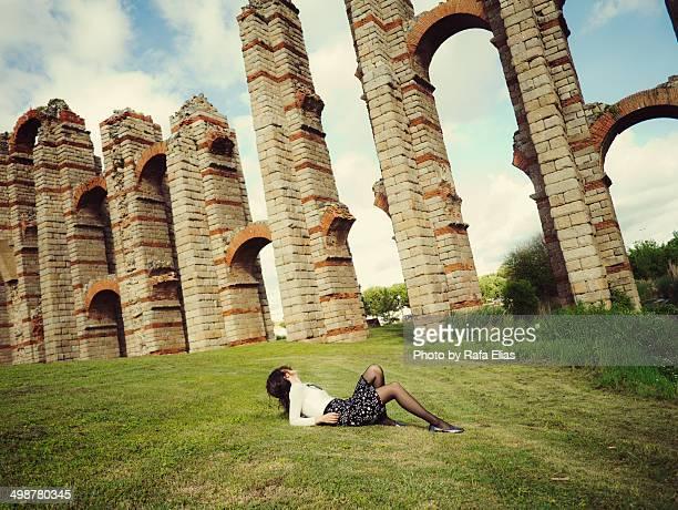 woman lying on grass next to roman aqueduct - extremadura fotografías e imágenes de stock