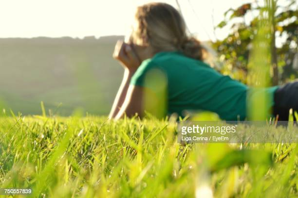 woman lying on grass - liga cerina stock pictures, royalty-free photos & images
