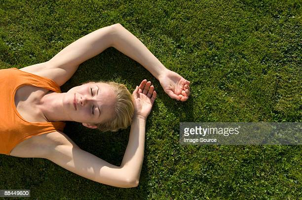 woman lying on grass - sunbathing stock pictures, royalty-free photos & images