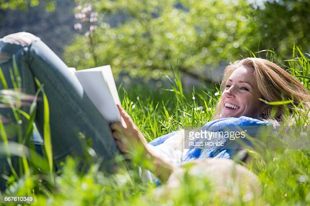 Woman lying on grass reading