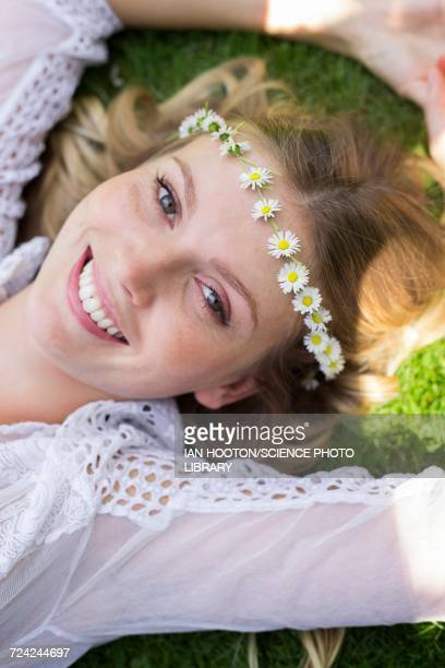 Woman lying on grass wearing daisy chain