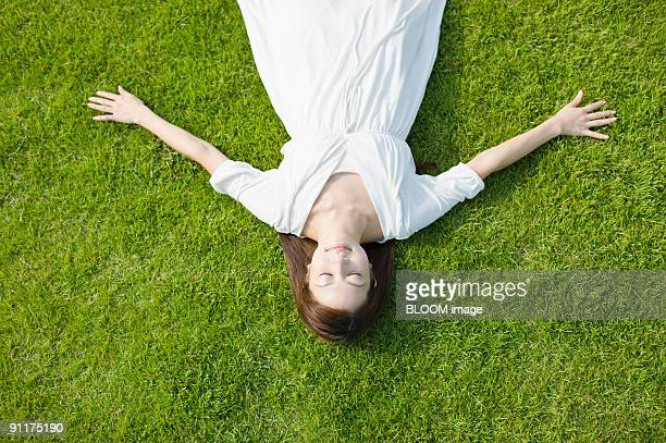 woman lying on grass with eyes closed - lying on back stock pictures, royalty-free photos & images