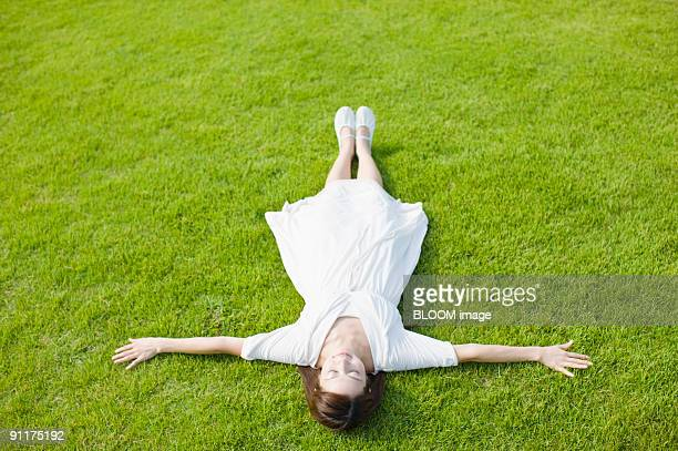 Woman lying on grass with eyes closed