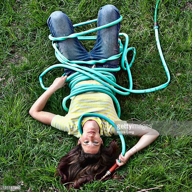 Woman lying on grass with garden hose
