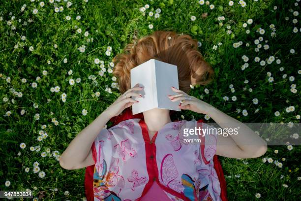 Woman lying on grass with her face obscured