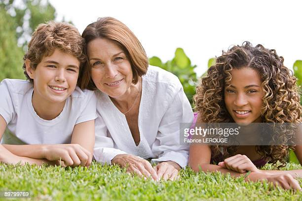 Woman lying on grass with her grandchildren