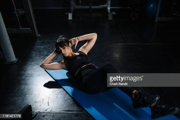 woman lying on her back doing cycling abs exercise - flat stomach stock pictures, royalty-free photos & images