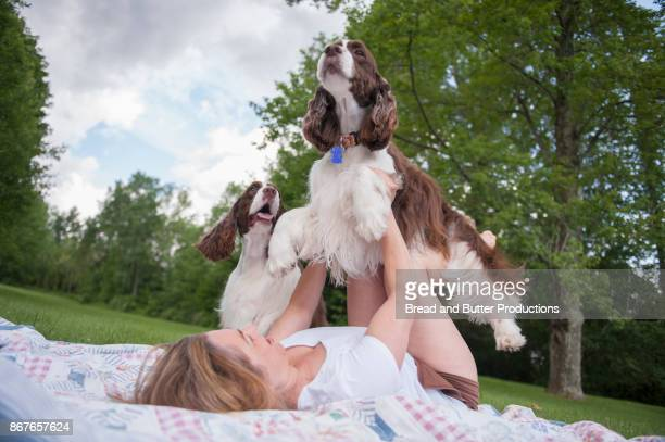 Woman Lying on her Back on Grass Holding Dog in Air while Second Dog looks on