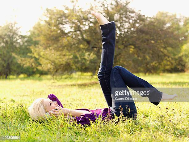 A woman lying on her back with her legs raised using a mobile phone