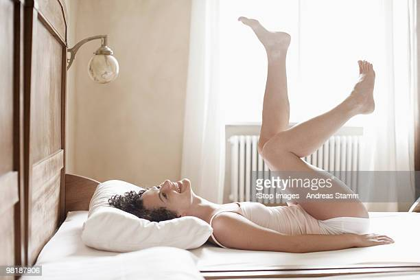 A woman lying on her bed with her legs in the air