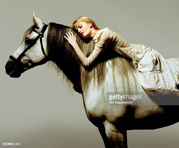 Woman lying on horse, eyes closed
