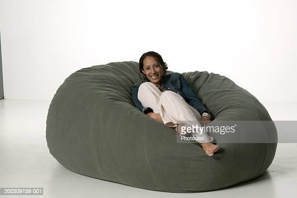 Woman lying on large bean-bag, posing in studio, portrait