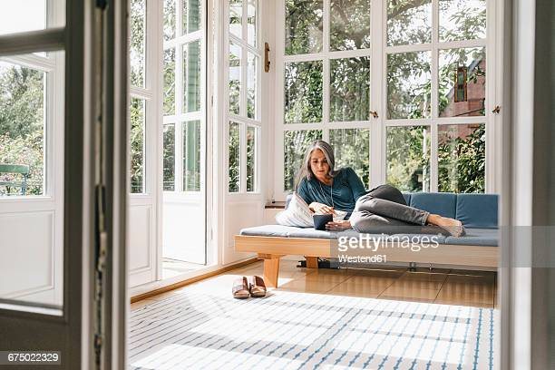 Woman lying on lounge in winter garden reading e-book