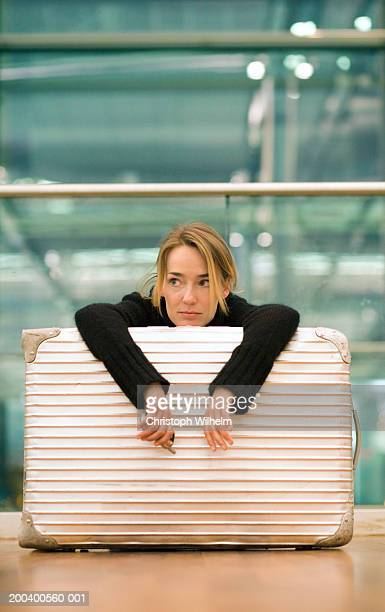 Woman lying on luggage in airport, close-up