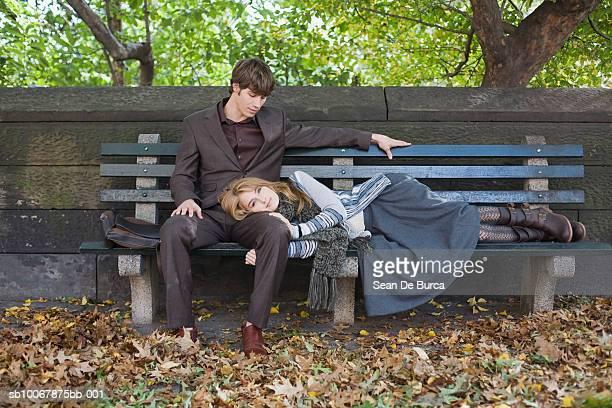 woman lying on man's lap at park - lying down photos et images de collection