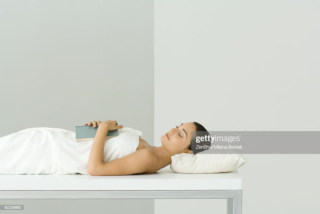 Woman lying on massage table, holding book on chest, eyes closed : Stock Photo