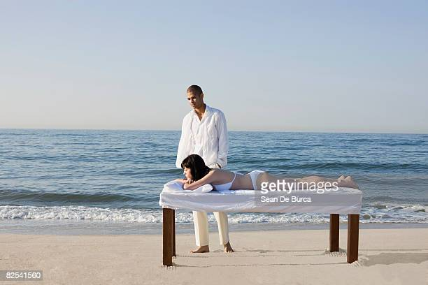 Woman lying on massage table with disconsolate man