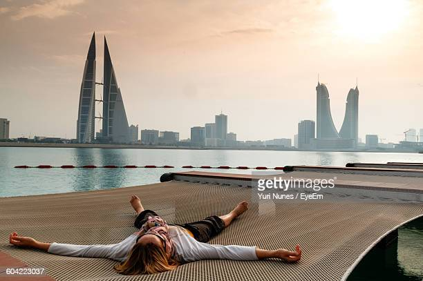 Woman Lying On Net At Pier Against Sky