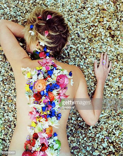 woman lying on pebbles with flower petals on her back - maya desnuda fotografías e imágenes de stock