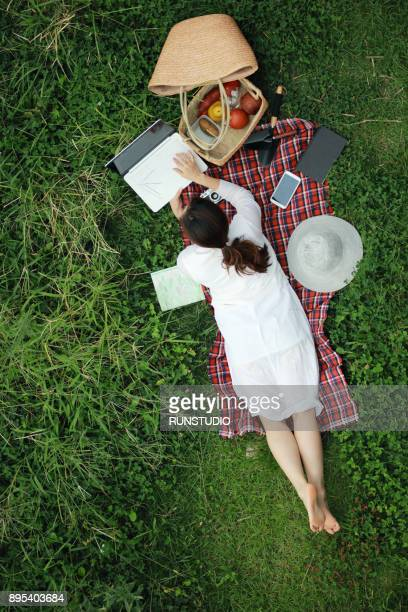 Woman lying on picnic blanket and using laptop