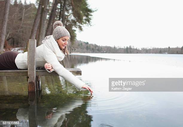woman lying on pier, touching surface of lake