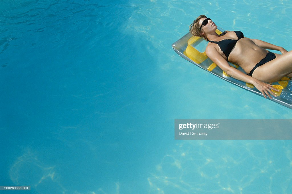 33160c61d Woman Lying On Raft In Swimming Pool Stock Photo - Getty Images