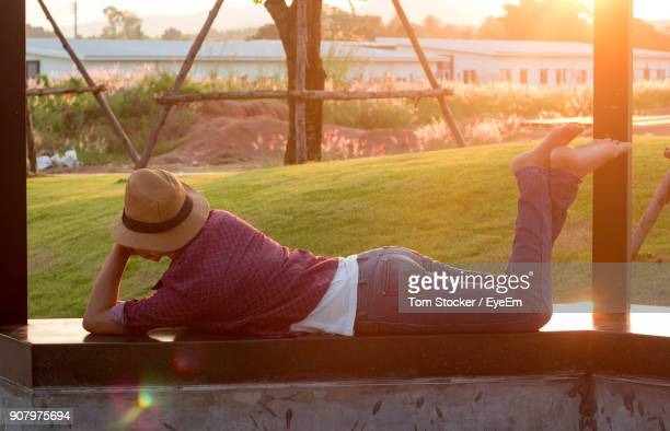Woman Lying On Railing During Sunset