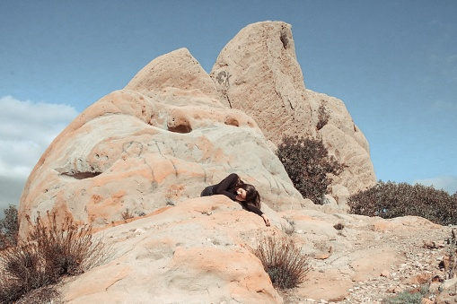 Woman Lying On Rock At Desert During Sunny Day - gettyimageskorea
