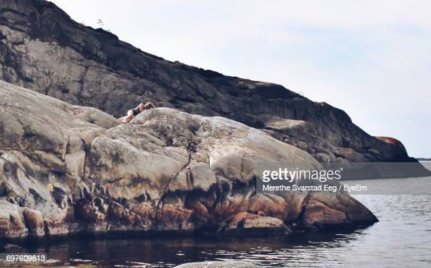 Woman Lying On Rock By Sea