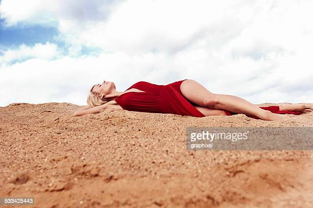 woman lying on sand - graphixel stock pictures, royalty-free photos & images