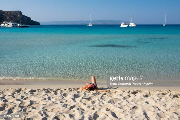 woman lying on shore against sea at beach - peloponnese stock photos and pictures