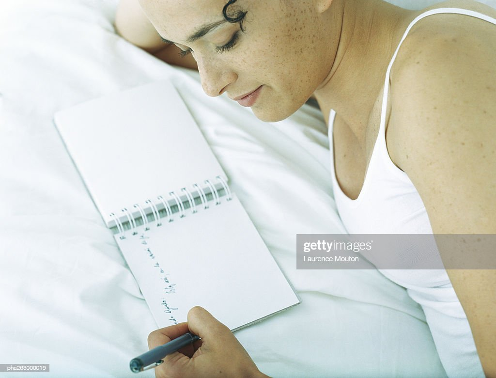 Woman lying on side on bed writing in notebook with pen : Stockfoto