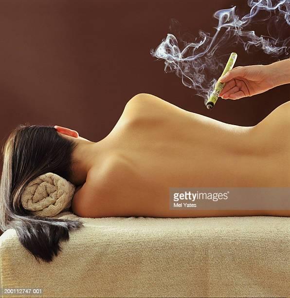 Woman lying on side, receiving cigar moxa treatment, rear view