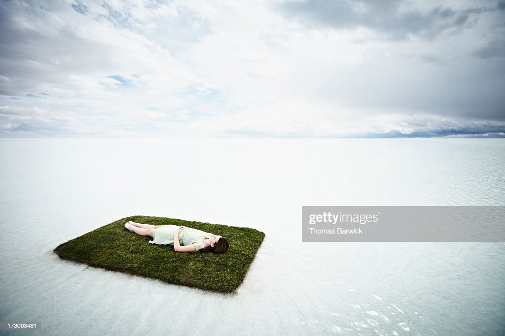 Woman lying on small island in large body of water : Stockfoto