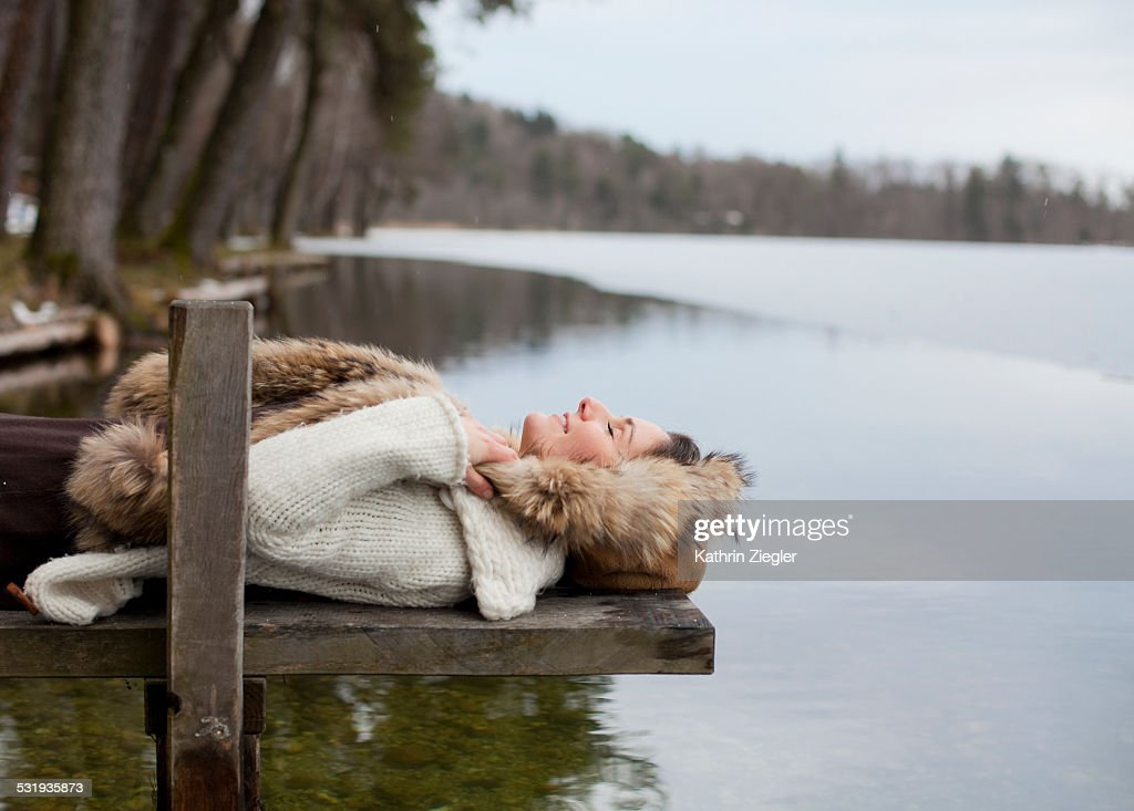 woman lying on small wooden pier with eyes closed : Stock-Foto