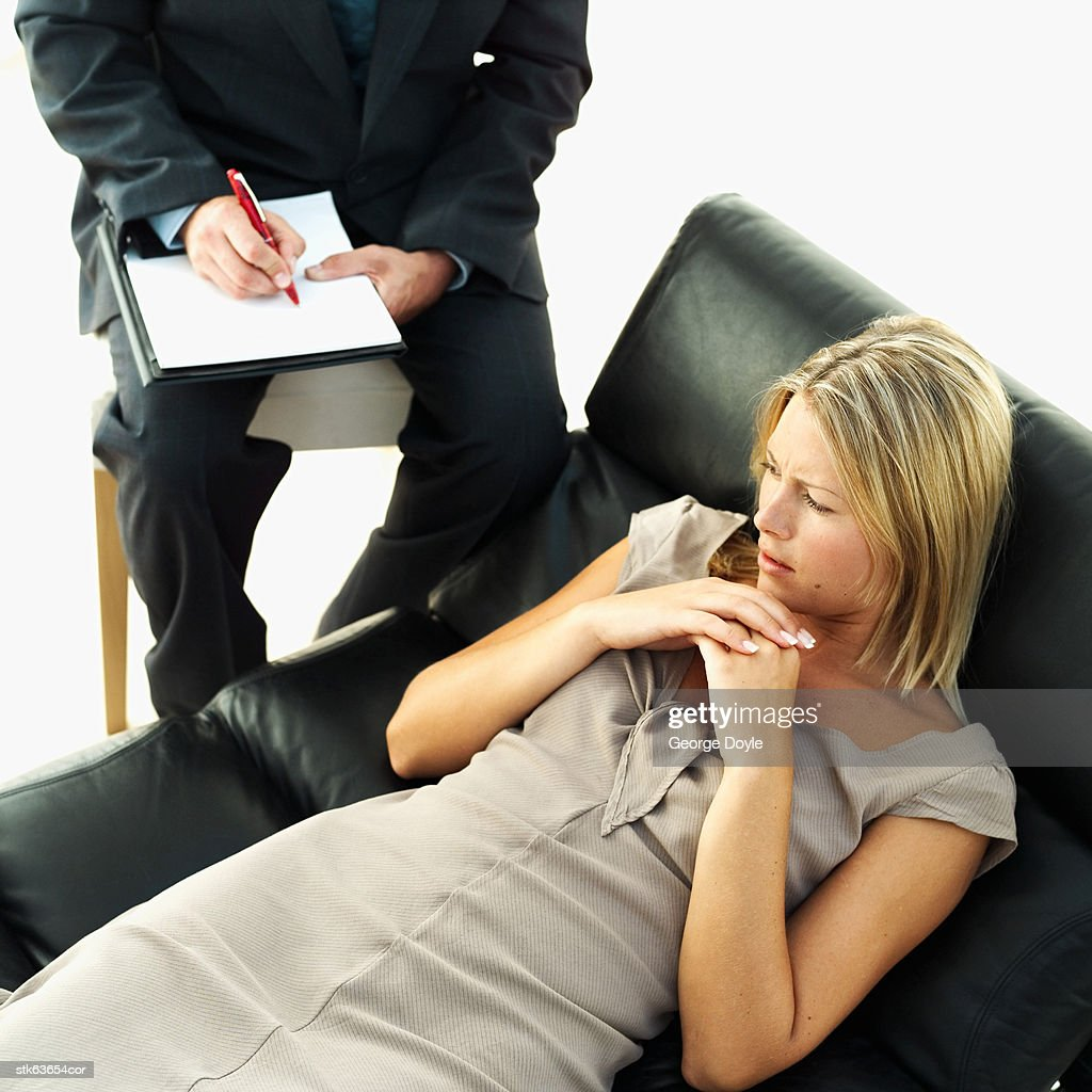 woman lying on sofa and man sitting besides her on chair writing : Stock Photo