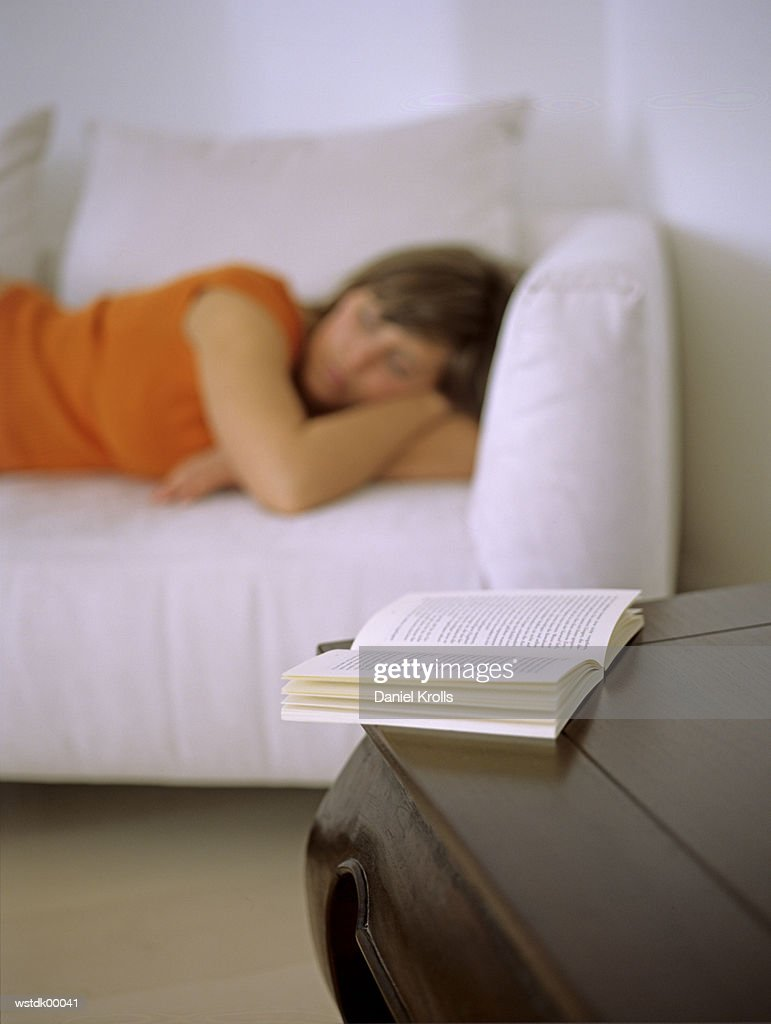 Woman lying on sofa, focus on open book : Stockfoto