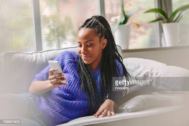 woman lying on sofa smiling at mobile phone - florence douillet photos et images de collection