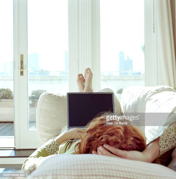 Woman lying on sofa, using laptop, rear view