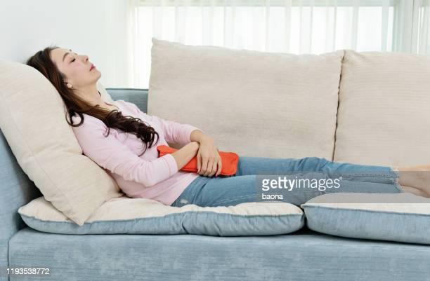 湯たんぽでソフォに横たわっている女性 - 下痢 ストックフォトと画像