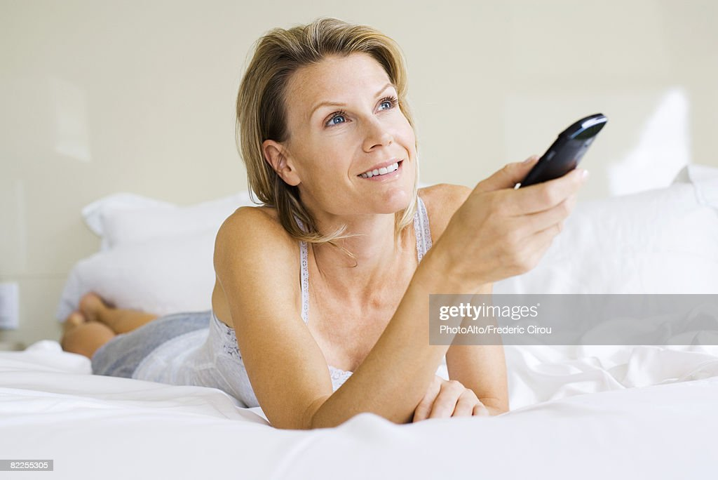 Woman lying on stomach in bed, holding remote control, looking up : Stock Photo