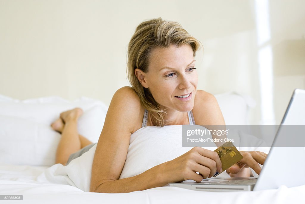 Woman lying on stomach in bed, using laptop and credit card : Stock Photo
