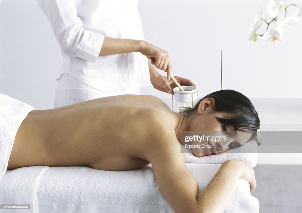 Woman lying on stomach on message table with eyes closed, mid section of woman standing behind : Stock Photo