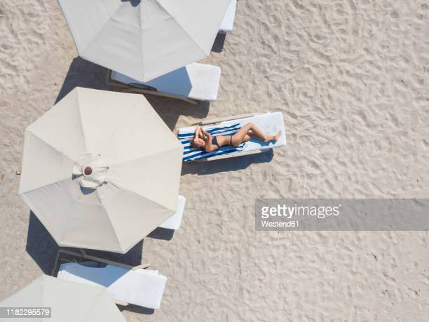 woman lying on sun lounger at the beach, gili air, gili islands, indonesia - parasol photos et images de collection