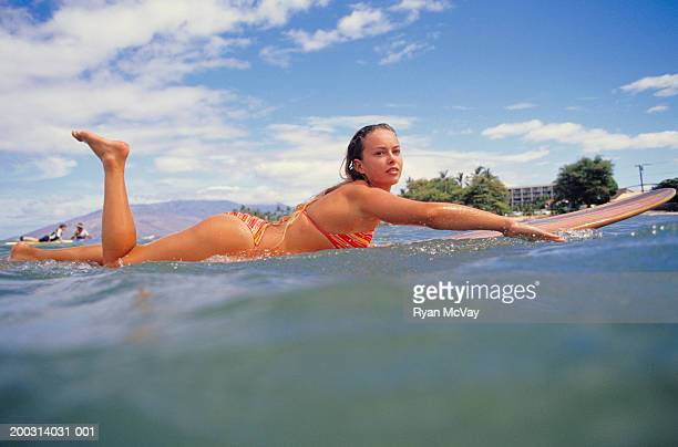 woman lying on surfboard in ocean, portrait, surface view - paddling stock pictures, royalty-free photos & images