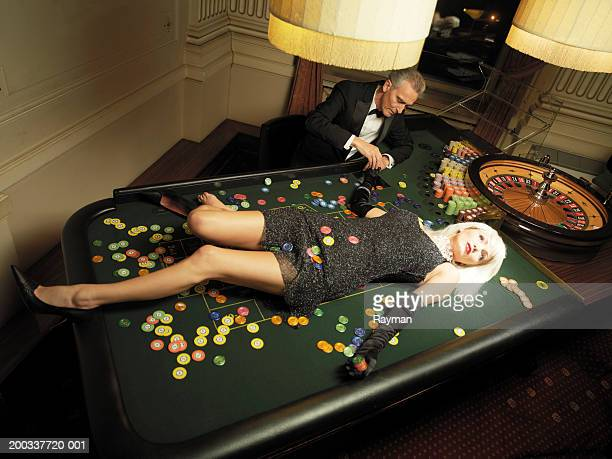 Woman lying on table by roulette wheel and croupier, elevated view