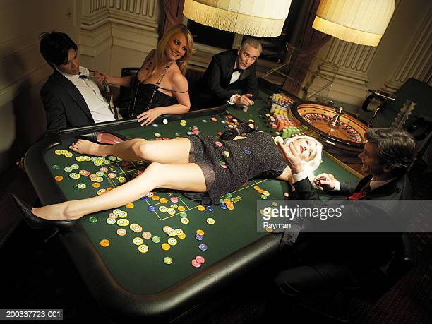 Woman lying on table by roulette wheel, croupier, and gamblers