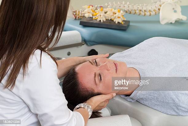 Woman lying on table while chiropractor massages neck