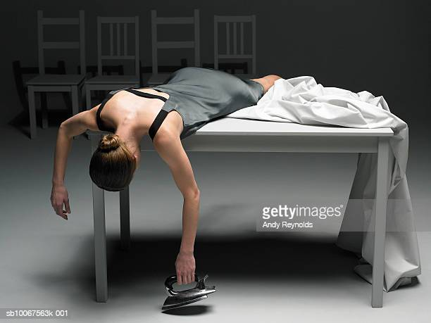 Woman lying on table with sheet holding iron