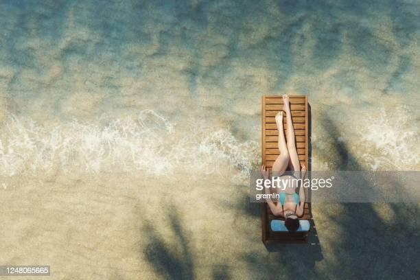 mulher deitada na praia - cadeira recostável - fotografias e filmes do acervo